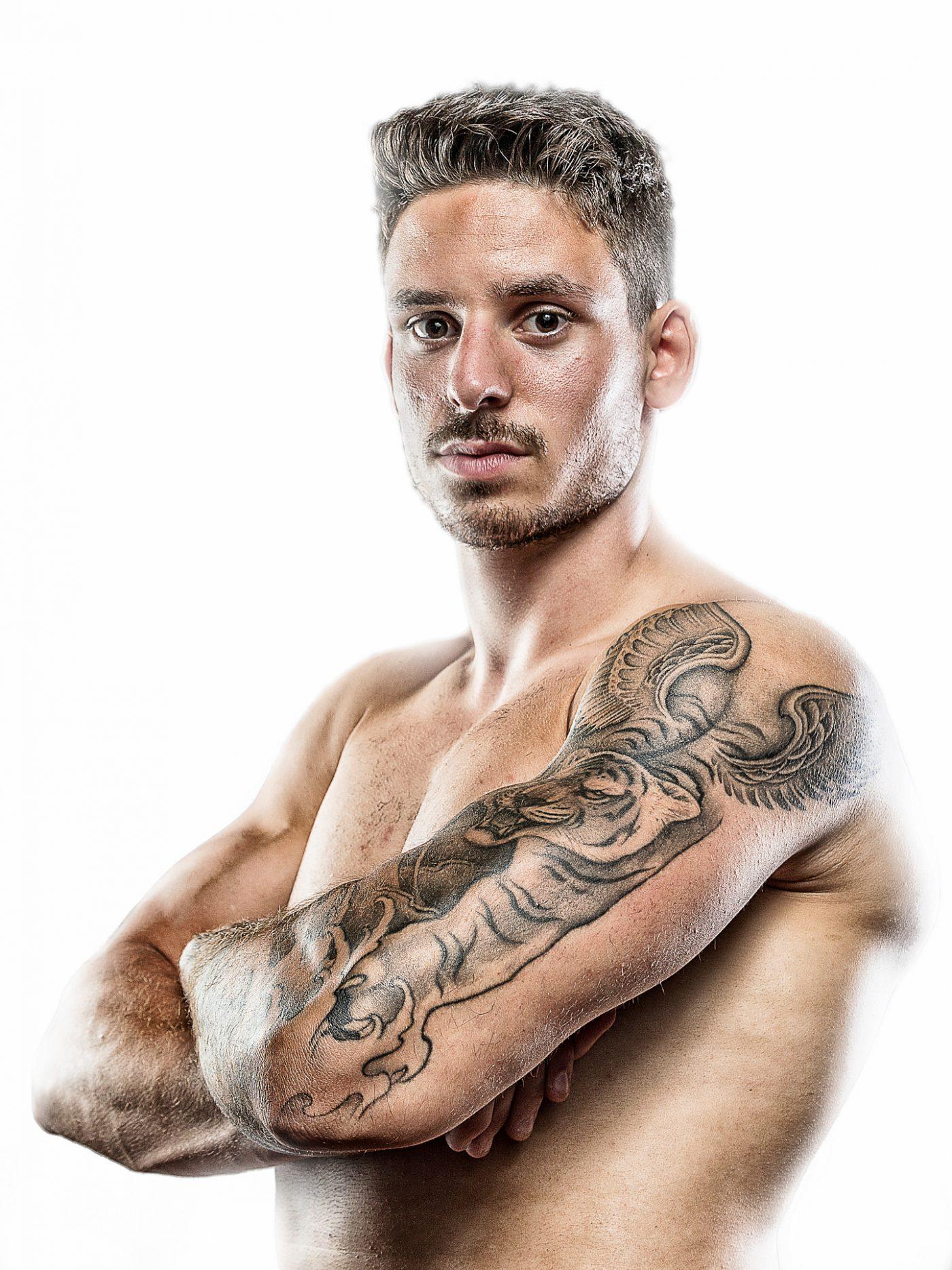 Portrait d'un d'un sportif sur fond blanc tatoué
