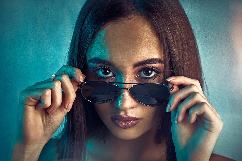 Portrait fashion d'un model avec lunette sur un fond bleu et coloré