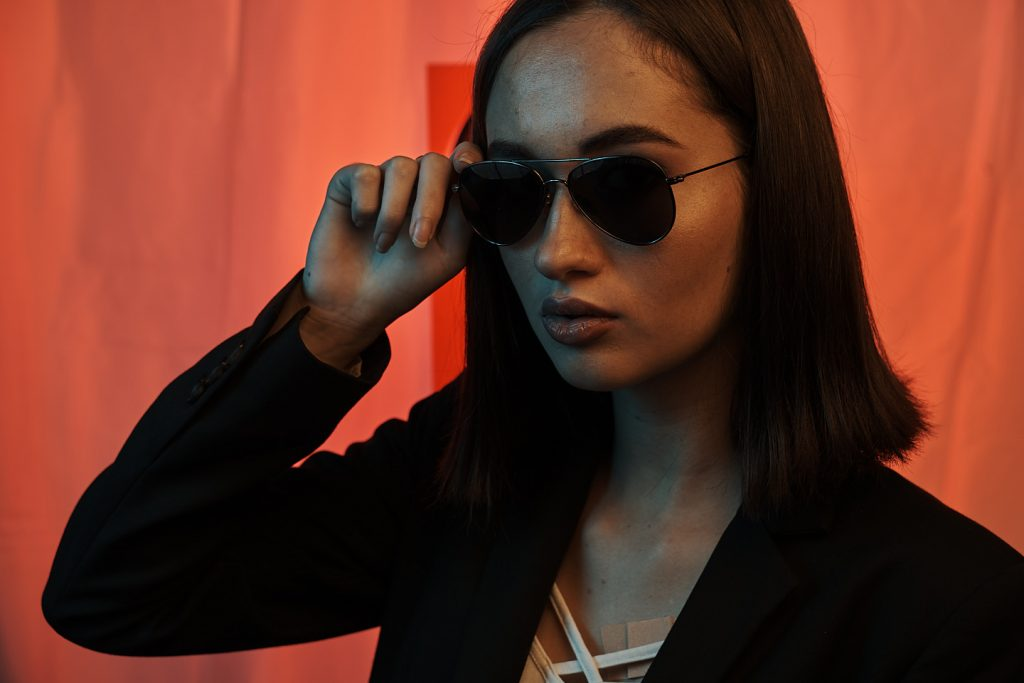 Portrait fashion d'un model avec lunette sur un fond sombre et coloré photo brute
