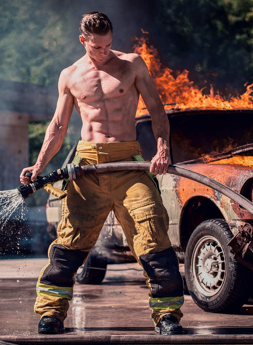 Homme pompier devant voiture en flamme