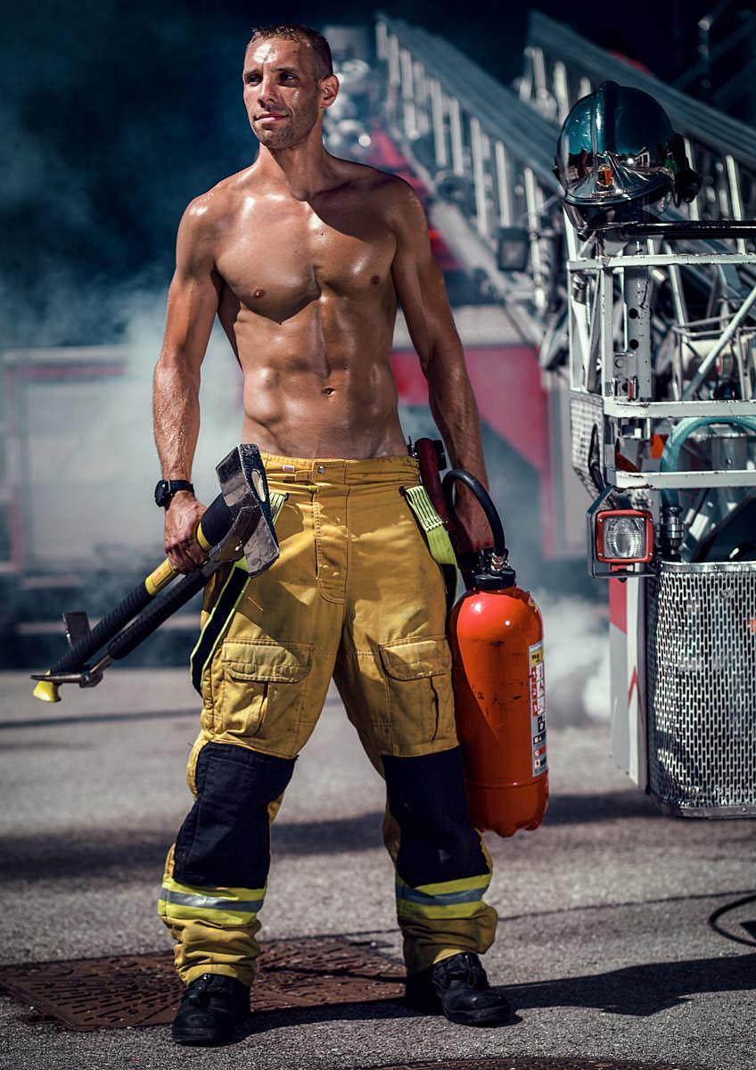 Homme pompier devant une échelle et accessoires dans les mains